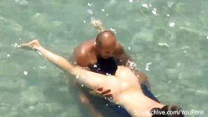Spy video of a naked couple making out at the beach